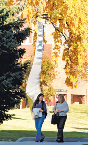two students walking through the main MSUB campus in autumn