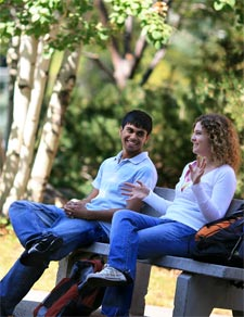 students sitting on a bench in Peaks to Plains Park on the MSUB main campus