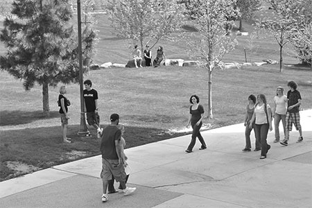 students walking and relaxing in Peaks to Plains Park outside the library