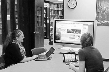 A PHOTO OF STUDENTS AT A COMPUTER IN THE LIBRARY