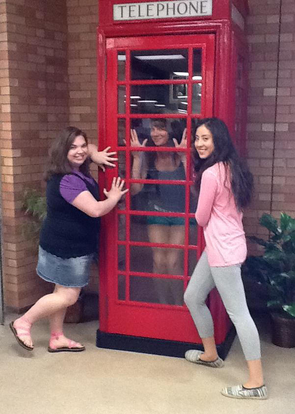 student workers hamming it up at the telephone booth in the library